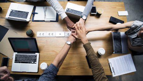 Garanzia Giovani Fase e il Reddito di Cittadinanza II, immagine di cinque mani di etnie diverse che si incrociano sopra un tavolo di lavoro in segno di collaborazione.