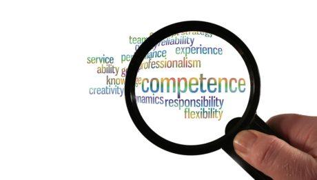 certificazioni delle competenze informale/NON formale. Immagine di una lente di ingrandimento che ingrandisce la parola Competence tra le altre di ambito lavorativo.