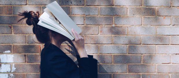 dispersione scolastica. Immagine con studentessa con libro in faccia