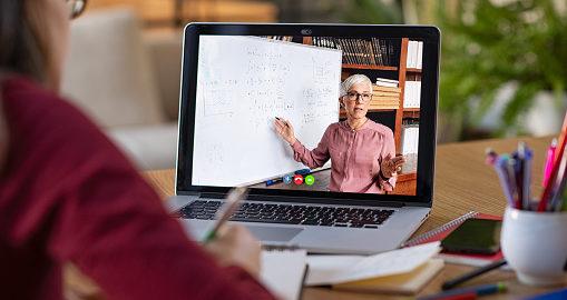 Studentessa prende nota davanti al pc. Dallo schermo si vede insegnante che spiega e scrive formula alla lavagna.