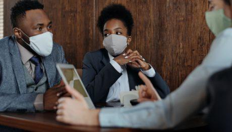 giovani fanno tirocinio con mascherine seduti a colloquio
